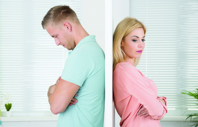 Unhappy Couple Standing Back To Back At Home