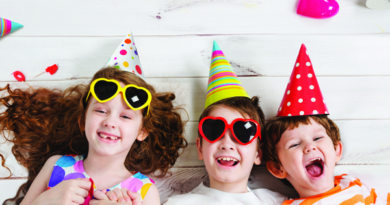 3 children laying down with party hats laughing